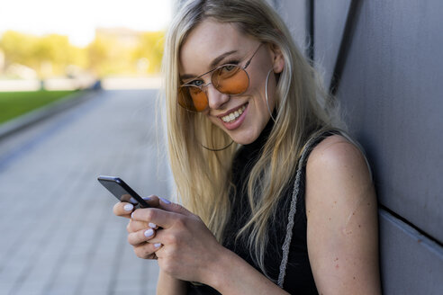 Portrait of smiling young woman using smartphone - GIOF06251