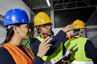 Man talking to female worker in factory workshop - ZEDF02080