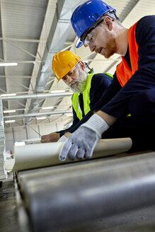 Two men working on plan in factory - ZEDF02086