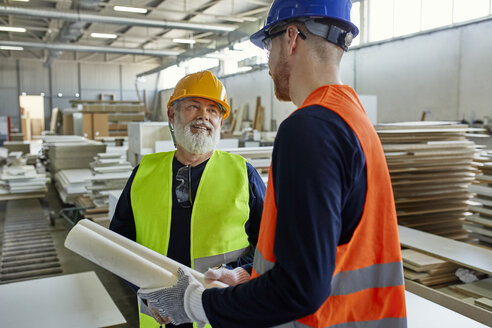Two men with plan talking in factory - ZEDF02089