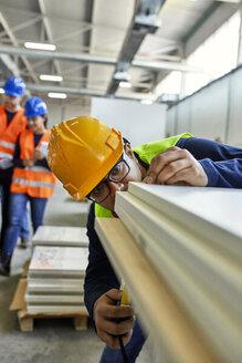 Worker examining wooden boards in factory - ZEDF02098