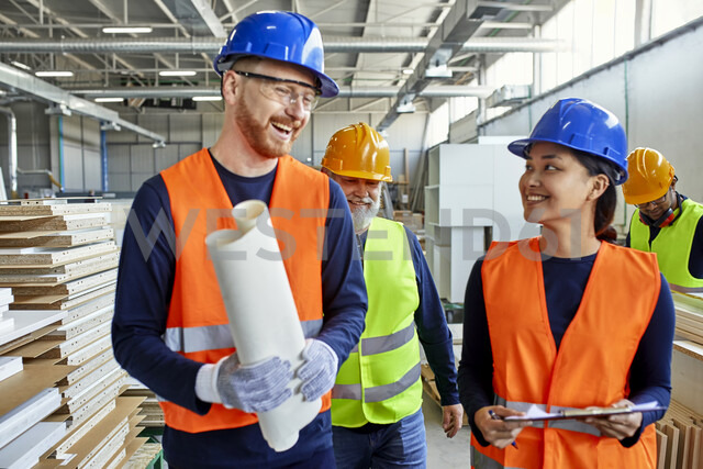 Happy colleagues in protective workwear talking in factory - ZEDF02101