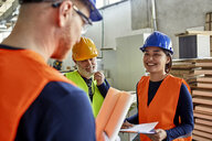 Colleagues in protective workwear talking in factory - ZEDF02107