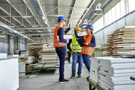 Happy colleagues in protective workwear high fiving in factory - ZEDF02110