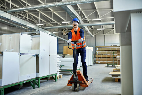 Laughing worker riding on pallet jack in factory - ZEDF02116