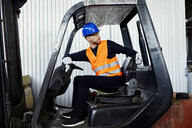 Worker on forklift in factory turning round - ZEDF02146