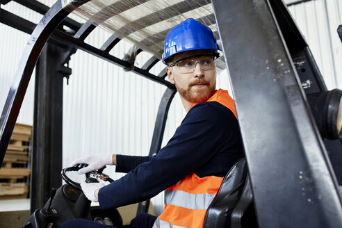 Worker on forklift in factory turning round - ZEDF02149