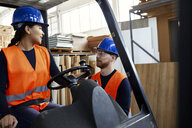 Man talking to female worker on forklift in factory - ZEDF02155