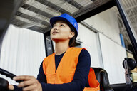 Female worker on forklift in factory looking up - ZEDF02158