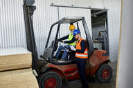 Man talking to worker on forklift in factory - ZEDF02161