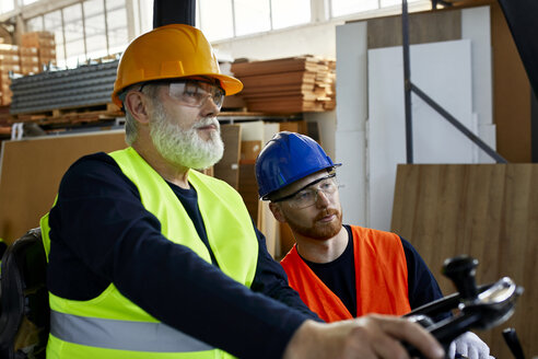 Two men with forklift in factory - ZEDF02164