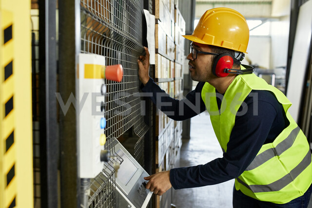 Man operating machine in industrial factory - ZEDF02173