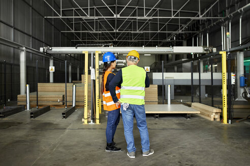 Rear view of male and female worker standing in factory workshop - ZEDF02179