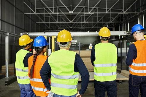 Rear view of workers standing in factory workshop - ZEDF02182