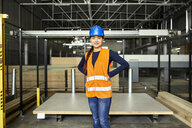 Portrait of confident female worker in factory warehouse - ZEDF02197