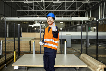 Portrait of happy worker with tablet in factory warehouse - ZEDF02200