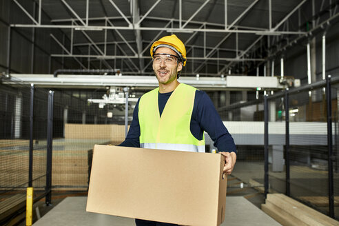 Portrait of smiling worker carrying box in factory warehouse - ZEDF02203