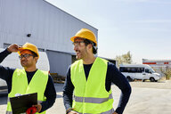 Two workers talking on factory yard - ZEDF02218