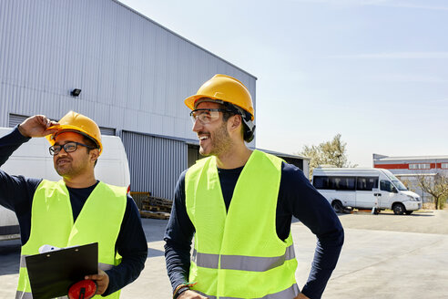 Two workers talking on factory yard - ZEDF02218