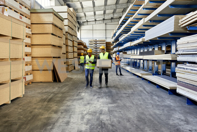 Workers moving and carrying boxes in factory warehouse - ZEDF02221