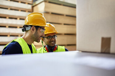 Two workers talking in factory warehouse - ZEDF02227