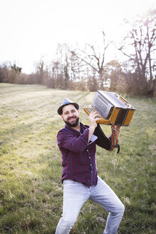 Portrait of smiling man with accordion on a meadow - HMEF00343