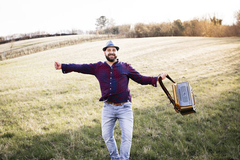 Man with black beard and hat playing the accordion, outside on a meadow, Lower Austria - HMEF00346