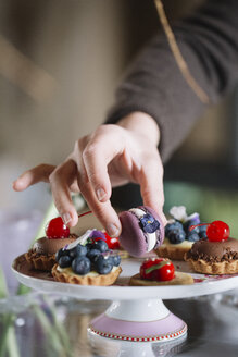 Woman's hand arranging Macaron on cake stand, close-up - ALBF00853