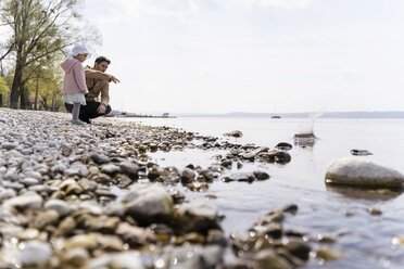 Germany, Bavaria, Herrsching, father and daughter on pebble beach at lakeshore - DIGF06740