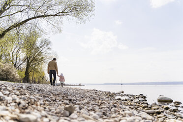Germany, Bavaria, Herrsching, father and daughter walking on pebble beach at lakeshore - DIGF06743