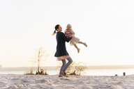 Germany, Bavaria, Herrsching, mother carrying daughter at the lakeshore at sunset - DIGF06746