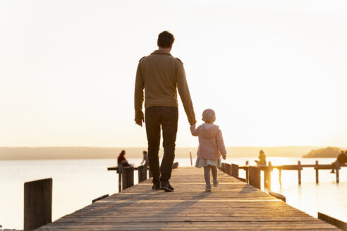 Germany, Bavaria, Herrsching, father and daughter walking on jetty at sunset - DIGF06749