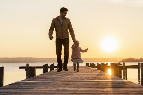 Germany, Bavaria, Herrsching, father and daughter walking on jetty at sunset - DIGF06752