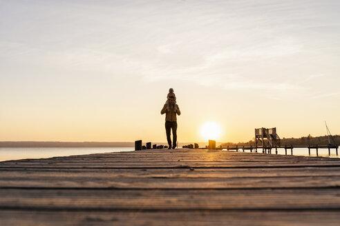 Deutschland, Herrsching, Vater 41 Jahre und Tochter 2 Jahre laufen zusammen auf einem Steg am See, Sonnenuntergang - DIGF06755