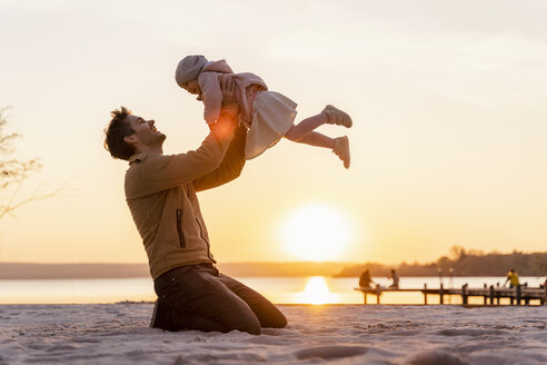 Germany, Bavaria, Herrsching, father and daughter playing on the beach at sunset - DIGF06758