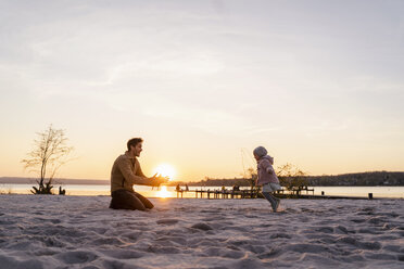 Germany, Bavaria, Herrsching, father and daughter playing on the beach at sunset - DIGF06761
