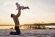 Germany, Bavaria, Herrsching, father and daughter playing on the beach at sunset - DIGF06764