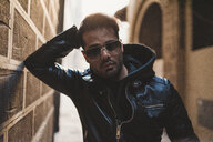 Portrait of bearded man wearing sunglasses and black leather jacket - FBAF00367