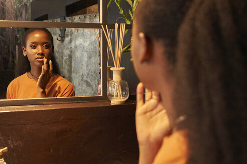 Woman touching up her makeup in the mirror. Botanica, Moçambique, Maputo. - VEGF00032