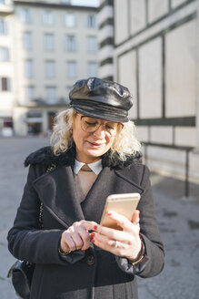 Italy, Florence, portrait of mature woman wearing black coat and leather cap using smartphone - FBAF00376