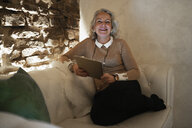 Portrait of happy mature businesswoman sitting on couch with digital tablet - FBAF00412