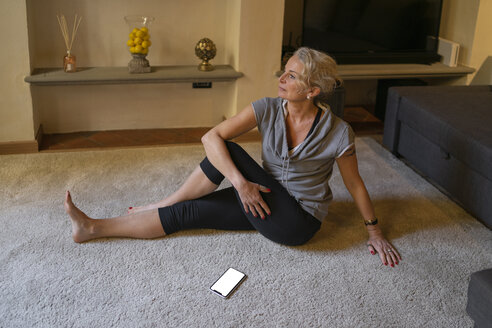 Mature woman doing Yoga exercise in the living room - FBAF00427