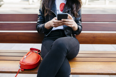 Young woman sitting on a bench, using smartphone - JRFF03087