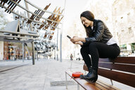 Young woman sitting on a bench, using smartphone - JRFF03090