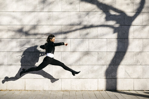 Spain, Barcelona. Brunette woman making a big jump on a white wall with a shadow of a tree in it. - JRFF03093