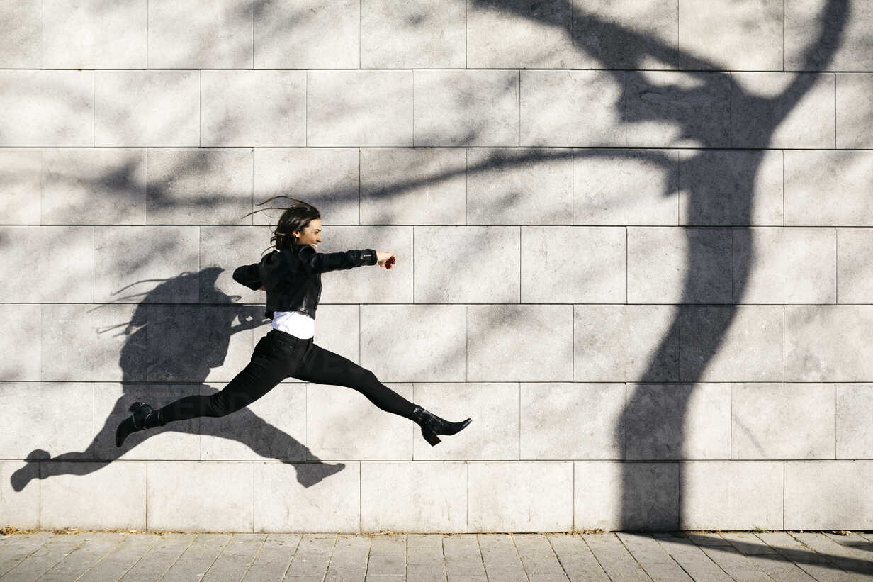 Young woman making a big jump on a  wall with a shadow of a tree - JRFF03093 - Josep Rovirosa/Westend61