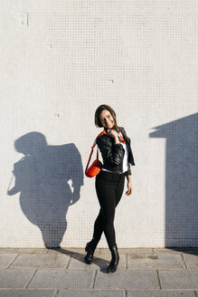Happy young woman with a red hip bag, wall in the background - JRFF03105