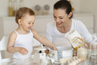 Happy mother and little daughter making a cake together in kitchen at home - DIGF06766