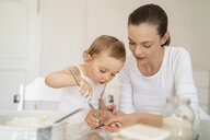 Mother and little daughter making a cake together in kitchen at home - DIGF06772
