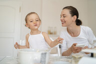 Happy mother and little daughter making a cake together in kitchen at home - DIGF06775